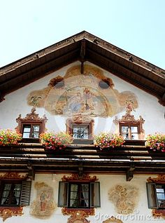 Photo made in Oberammergau in Bavaria (Germany). The picture shows the upper part of the facade of one of the typical houses of the country where almost all the houses are painted and some with scenes depicting fairy tales. In the image sivedono total of five, three lower and two upper, windows and a glass door leading to a wooden balcony on which are flowers of various colors. Above the balcony a large fresco with religious image.