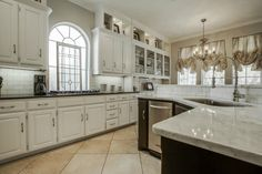 Lovely white kitchen with contrasting cabinetry and countertops // White outers with black granite, black island with white marble