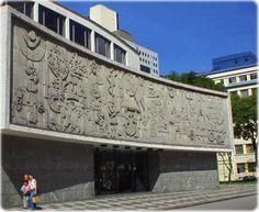 Painel pictográfico da história do teatro no mundo, de autoria de Poty Lazzarotto. Trabalho em alto relevo na parte frontal do Teatro Guaíra, Curitiba. Guia Geográfico.