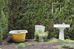 An Outdoor Bathroom in the children's garden, a small area with bathroom objects, a pedestal basin and toilet, and a bath planted with plants and shrubs.