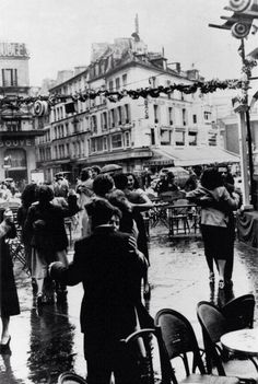 Couples dancing in the rain on the streets of Paris, celebrating July 14th (France's national holiday) 1954