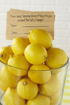Lemon Cylinder. Fill a large glass cylinder with lemons, then let guests guess how many lemons it takes to reach around mom and her baby bump.
