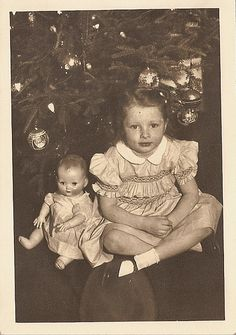 .Girl with doll sitting under Christmas tree vintage photograph