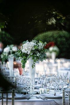 Centrotavola con vasi alti e fiori per tavoli imperiali di nozze