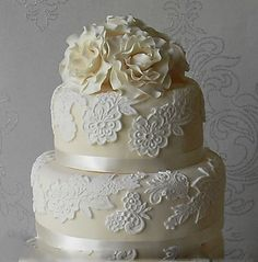Ivory fondant covered wedding cake overlaid with white lace motifs and topped with sugar paste roses