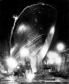 Towering above the King George V drydock at Southampton is the gigantic hull of the Cunard-White Star liner Queen Mary, outlined by the night sky by floodlights as she undergoes a six week overhaul and renovation. 10th November 1949