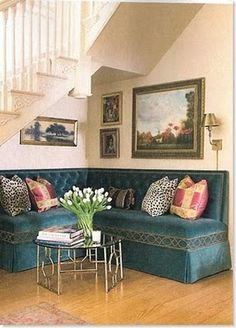 great use for space under stairs, gorgeous velvet tufted sofa and landscapes!