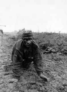 A young Soviet soldier, severely injured, crawls towards his German captors after surrendering during the Battle of Kursk.