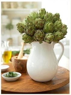 an idea for those clear glass pitchers we never sell. put an arrangement inside them, not necessarily artichokes