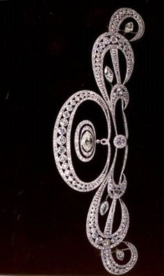 A diamond and platinum 'transitional' tiara, composed of a central openwork oval motif of graduated circular-cut diamonds within a tapering line of smaller diamonds above and below and supporting in the center a large marquise-cut diamond within two graduated oval halos, a large circular-cut collet below, and to either side three graduated stylized 'C' scroll motifs, each with a central marquise collet set throughout with brilliant-cut diamonds, probably French, circa 1912.