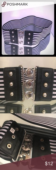 Black/white stripe wide stretch belt 3 connects/ This belt is in size medium/large it is a stretchy 3 inch wide black stretch belt with vegan leather on the front side decorated by three studs on each piece of the vegan leather it has silver hardware and a slide and connector and three different spots as pictured. There are a few scratches on the hardware but it's really not a big deal. It is also flattering It can go with about anything! The  pictures are description/items are as is via…