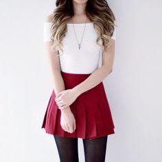 White top w/ shoulder sleeves, a plain red pleated skirt, black leggings.