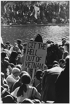 """Vietnam War Protest in Washington, D.C. by Frank Wolfe, October 21, 1967. A protest sign reads """"GET THE HELLicopters OUT OF VIETNAM""""."""