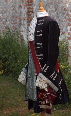 """Taken from an original pattern, the jacket and breeches are tailored from grey cotton velvet and lined with silver Duchess-silk; decorated over dimensional buttonholes of metallic-silver braids accentuated with plasticity the opulence and fullness of velvet material. The higher status of Aristocrats is typified by a wide sash from wine-red coloured silk taffeta, edged with a silver braid."" (http://diekostummacher.com/Barock.aspx)"