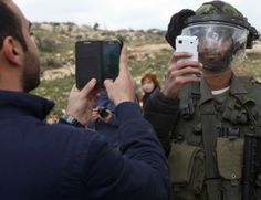 CISJORDANIE, Nabi Saleh. Un Palestinien et un membre des forces de sécurité israéliennes prennent une photo l'un de l'autre avec leurs téléphones portables après une manifestation de Palestiniens contre des colons juifs et la colonie juive de Hallamish, le 14 mars 2014. AFP/Abbas Momani