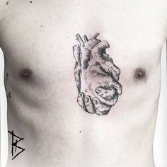Engraving style anatomical hand heart tattoo on the sternum.