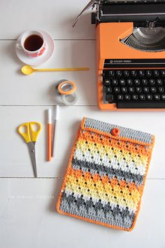 Crochet sleeve for iPad or tablet in orange, yellow, and gray.