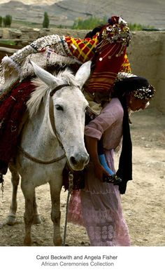 Africa | The veiled Berber bride travels on mule back from her parent's home to the village of her husband's family.  Morocco | ©Carol Beckwith and Angela Fisher
