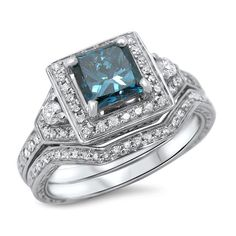 This magnificent ring set boasts a blue princess-cut diamond masterfully set in a four-prong setting. Round diamonds surround the solitaire on its engagement ring and are set on the matching 14k white gold band.
