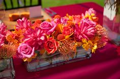 The reception decor stayed true to the couple's fuschia and orange color scheme. This bold and bright centerpiece featured lush roses, protea, and craspedia. | Photo by Rachel Robertson Photography, Floral Design by Flowergirls