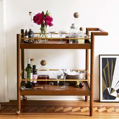 Bar on the move! Equipped with two shelves and a set of handy wheels, west elm's Mid-Century Bar Cart makes a great tableside-serving station or cocktail perch.