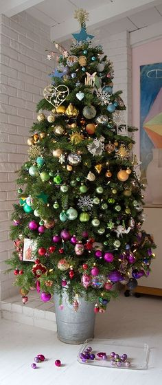 christmas tree decorated with 'layers' of colour - baubles of different colours grouped by colour and in layers