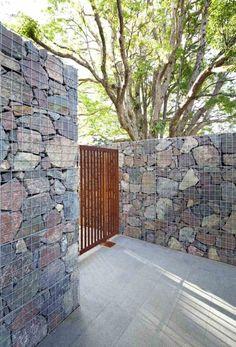 mur gabion moderne en grands blocs de pierre grise et porte de jardin en acier corten