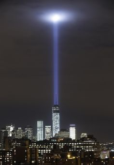A test of the twin beams of the Tribute in Light intersect with still-under construction Tower One as they rise behind the building and above lower Manhattan, Monday, Sept. 9, 2013, in New York. The memorial, sponsored by the Municipal Art Society, will light the sky on the evening of Sept. 11, 2013, in honor of those who died in the Setp. 11, 2001, terror attacks on the United States. (AP Photo/Kathy Willens)