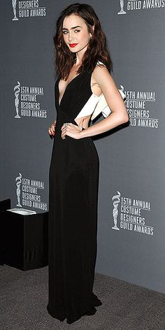 Lily Collins in black gown with an oversized bow on the back at the Costume Designers Guild Awards in Beverly Hills