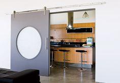 A cozinha tem porta de correr com roldanas que deslizam por trilho do lado externo. A cozinha é incorporada à área da churrasqueira e do forno de pizza por uma janela com painéis de vidro