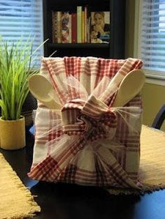 Gift idea ~ 1 cookbook, A couple wooden spoons (or spatula's or kitchen utensils), 1-2 kitchen towels (depending on the size of the cookbook), Tulle, raffia, or ribbon @ DIY Home Ideas