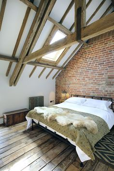 Farmhouse style bedroom with wooden ceiling beams, skylight and exposed brick…