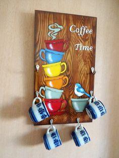 Porta-xícaras confeccionado em Mdf com imitação de madeira de lei, pintura à mão com auxilio de stenceis com fina camada de verniz especial para proteger a peça.    Os ganchinhos são de metal na cor prata e este porta-xícaras acomoda meia dúzia de xícaras de café ou de café.    OBS. AS XÍCARAS NÃ...