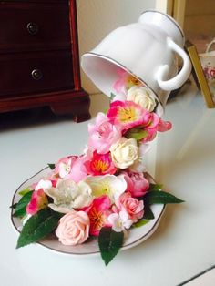 Floating teacup made by gluing a bent spoon into the cup and onto the plate, then covering it with flowers.