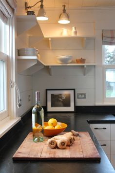 Exquisite Cottage home renovations Rustic Kitchen Portland Maine home insurance black counters cottage cutting board flush cabinets harbor open shelves roman shade soapstone wall sconce white painted wood - Decorcology.com