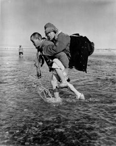 Korean carries his aged father across the icy Han River at Chungju, Korea, in their flight to the south to escape the onrushing communists.