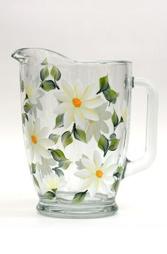 Creamy white daisies with yellow centers and deep green leaves hand-painted encircling quality tall pitcher. Also available in a 5 or 7 piece hostess set with footed goblets. Sealed and heat-cured for Glass Ceramic, Ceramic Art, Donna Dewberry Painting, Wine Images, Painted Wine Glasses, Clay Pots, Bottle Crafts, Glass Design, Colored Glass