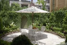 The walled courtyard garden is lush with jasmine, hydrangeas, orange trees, and creeping fig.crushed oyster shells cover the ground. The iron table and antique French garden chairs are shaded by a Pottery Barn umbrella. Garden design by Marshall Stone. Outdoor Rooms, Outdoor Decor, Walled Courtyard, Row House, Beautiful Backyards, Backyard Landscaping Designs, Garden Layout, Garden Chairs, Small Courtyards