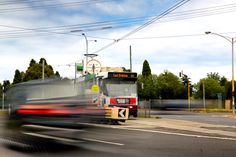 L1M2AS3. Tv Mode. BLURRED MOTION. 0.4sec, f/7.1, 70mm, ISO 100. Taken outdoors, tripod, ND filter as it was midday. Focus is on tram. Leading lines above and below the tram, showing two cars in blurred motion, one on the foreground and another one on the background.