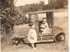 Vintage photo of toddler and baby with toy pedal car