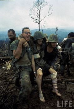 American Marines aid a wounded comrade during intense battle for Hill 484 as part of Operation Prairie being conducted near the DMZ during the Vietnam War.