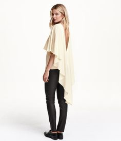 Sleeveless jersey top with a circle-cut cape in crêpe. Top with low-cut V-neck at back. Cape with longer, divided back section.