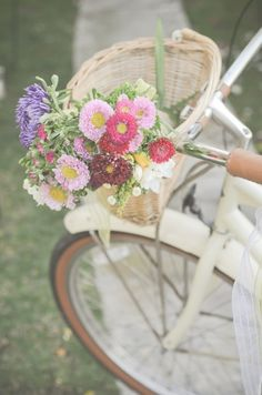 A white bicycle with a basket of flowers