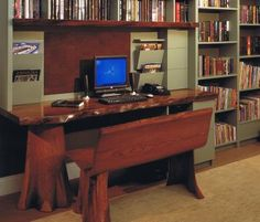 The computer desk was built by a natural woodworker who used a tree stump for the main support to the desk and bench, and a natural tree slab for the desktop. Alternating shelves are built out of natural tree slabs combined with laminate shelving. Natural cork provides the surface for the bulletin board.
