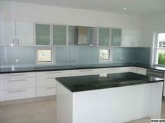 white kitchen, dark benchtop & window with sink on side