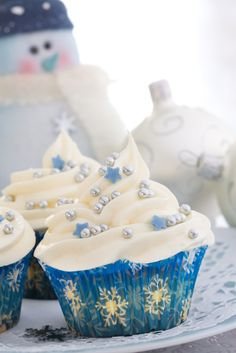 White frosted Christmas cupcakes in pretty blue wrappers decorated with silver dragees and blue snowflake quinns.