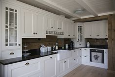 Hamran Kitchen. Extraordinary kitchens from Norway. Traditional kitchen inspiration. Scandinavian design. Black granite worktop. Lacquered white mdf cabinets. Cabin Kitchen. Miele appliances. Kitchen island. Recessed doors, the inner edge of the frame is profiled.