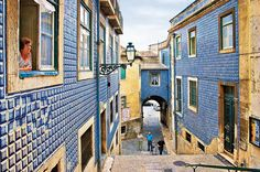"""Alfama Se a ideia é conhecer o lado mais tradicional de Lisboa, então Alfama é obrigatória. É fácil perder-se no labirinto de ruas estreitas do bairro que sobreviveu ao terramoto de 1755 e que dá morada a alguns dos mais """"castiços"""" estabelecimentos da capital. A cada curva descobrem-se becos, largos e pátios, alguns deles muito bonitos como a Calçadinha de Santo Estêvão e também as fontes mais antigas da cidade, como o Chafariz Real e o Chafariz de Dentro."""