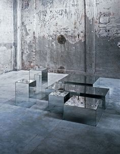ILLUSION Design: Jean-Marie Massaud Series of parallelepiped shaped low tables with mirroring top and degrading shading mirroring sides. Realized in extralight glass, glued 45°.