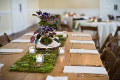 Tablescape on farmhouse table with moss runner, violets, and votives